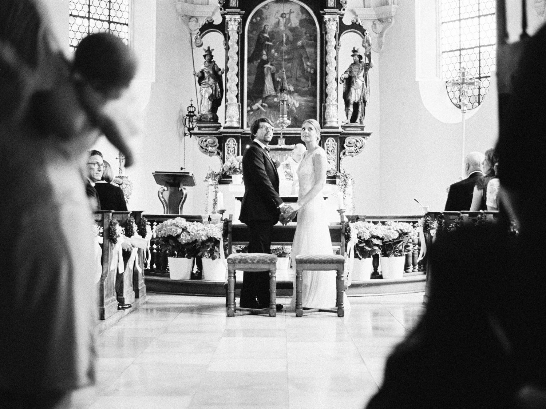Kirchliche Trauung Hochzeit Müchen Innenstadt Isar Brautpaar schaut dem Hochzeitssänger zu Hochzeitsfotograf JungetrifftMädchen